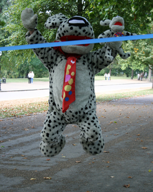 Spotty the Dog - Lynn's Bowel Cancer Campaigns mascot - jumping for joy at the finish line